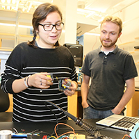 Kelly Rodriguez-Vasquez demonstrates the AIRduino device in the lab with Nathan Kidwell