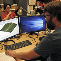William & Mary Ph.D. student Shuangli Du and staff scientist Dr. Doug Beringer working in front of computers inside William & Mary's Ultracold AMO Physics Laboratory.