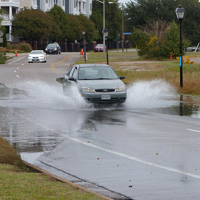 A car drives through water on a roadway