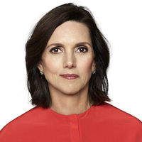 Beth Comstock wearing a red shirt and standing in front of a white backdrop
