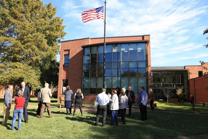 People stand around a flagpole with an American flag flying atop