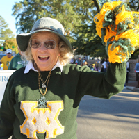 A person in a green W&M sweater waves a pompom in a parade