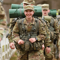 A soldier in uniform smiles at the camera while marching with others