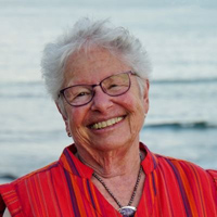Professor Iris Anderson stands in front of a body of water and smiles at the camera