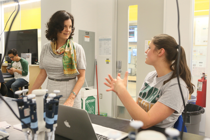 Katherine Rowe talks with a student in a lab with equipment around them