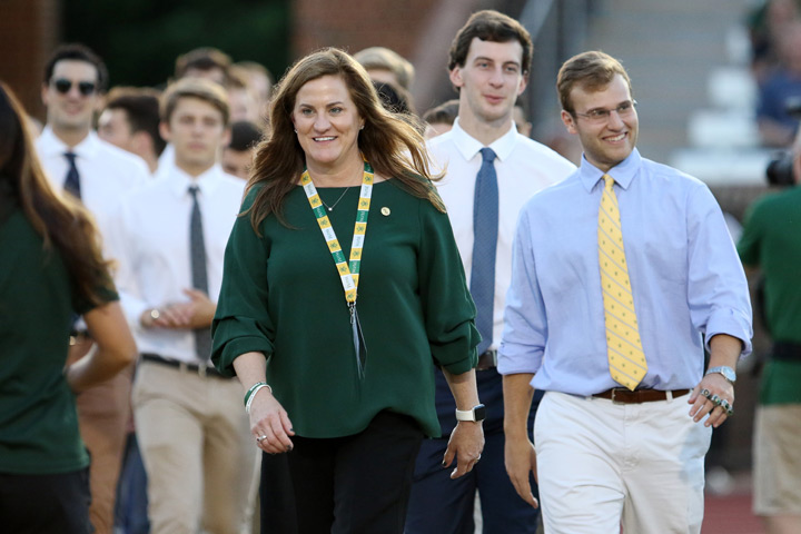 Samantha Huge leading W&M's CAA champion men's swim team during on-field recognition