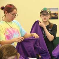 Student work on transforming shirts into bags. (Photo by Stephen Salpukas)