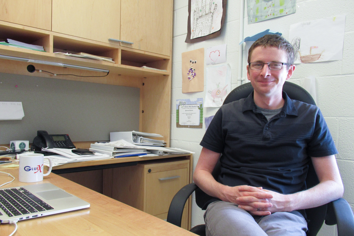 Physicist Justin Stevens is pictured sitting in his office at Small Hall at William & Mary