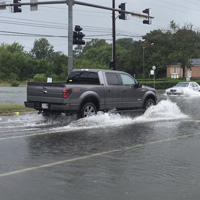 A pickup truck drives through a flooded intersection, splashing water