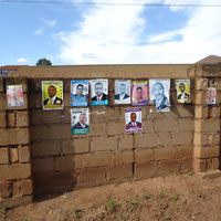 Brick wall papered with Uganda election posters