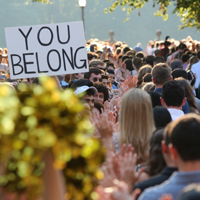 "A sign saying ""You Belong"" is held up among a large crowd outside of the Wren Building"