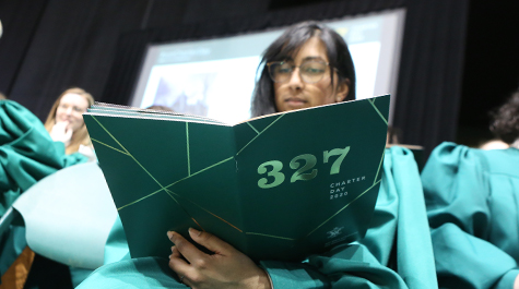 A person in a choir robe looks at a program with a green cover and 327 on it