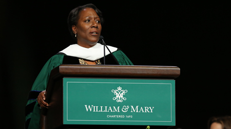 Christy Coleman dressed in academic regalia at a podium