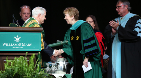Susan Magill dressed in academic regalia shakes the hand of Robert Gates on a stage