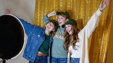 Three students pose in front of a gold background in a photo booth