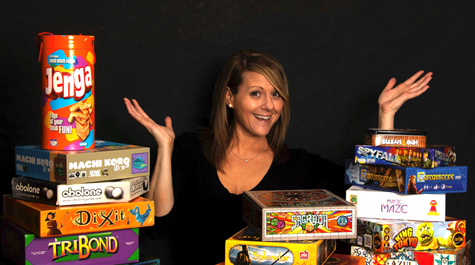 Michele King surrounded by piles of board games