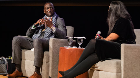 Yusef Salaam talks with Stephanie Walters while both are seated on a stage