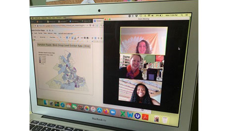 Laptop with screen showing graphic of Virginia map on left side and three women videoconferencing on right side
