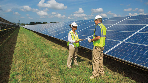 Two people in hard hats stand near solar panels in a large field