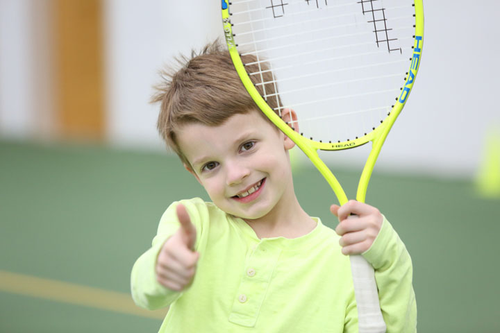 A child gives a thumbs-up while holding a tennis racket