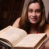 "Caitlin Dolt '22 stands beside the Swem Special Collections' copy of Isaac Newton's ""Principia."""