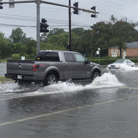 A truck drives through flooding on a roadway