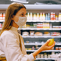 Woman grocery shops while wearing a face mask