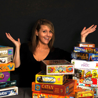 Michele King surrounded by a pile of board games