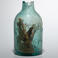 "Glass jug filled with nails that is believed to be a rare ritual item known as a ""witch bottle."""