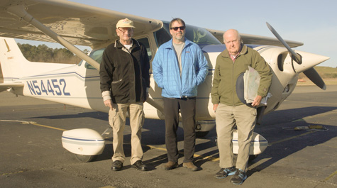 Fuzzzo Schermer, Bryan Watts and Mitchell Byrd stand in front of the airplane
