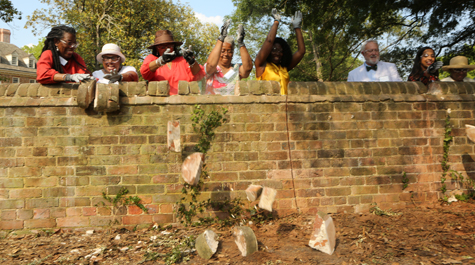 People push bricks off of the top of a brick wall