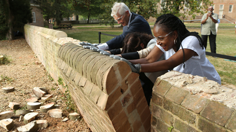 Taylor Reveley, Katherine Rowe and Jody Allen push over a section of wall