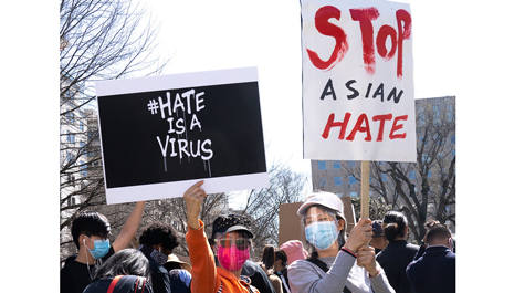Two people hold up signs that say Hate is a Virus and Stop Asian Hate