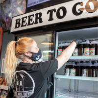 A person wearing a mask and gloves reaches into a cooling case that says Beer To Go on the top
