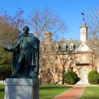 The statue of Lord Botetourt stands in front of the Wren Building on a sunny day
