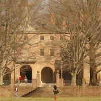 People walk in the Sunken Garden during a fall day with the Wren Building in the background