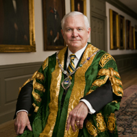 Robert Gates wears his green and gold chancellor's regalia while sitting in the hall of presidential portraits