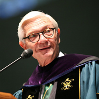 President Taylor Reveley wearing regalia stands at the podium of an event