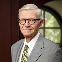 President Taylor Reveley in a suit standing in the Great Hall with window in the background