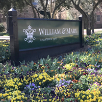 William and Mary campus sign surrounded by spring flowers.
