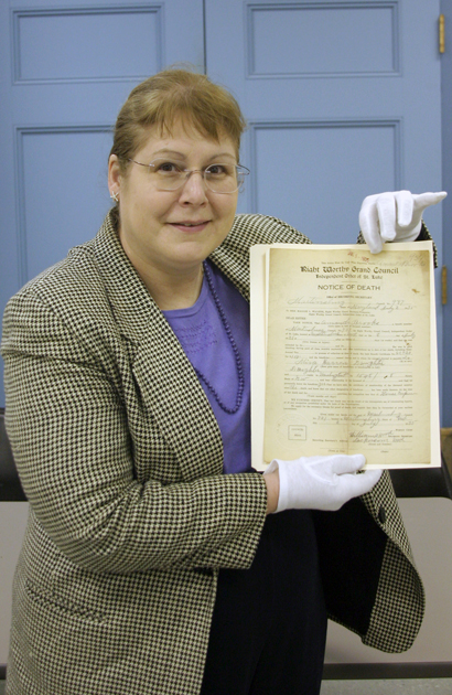 Heather Huyck displays the 1935 death certificate of Amanda Brooks. It's one of scores of documents found by the Sharpe Seminar.