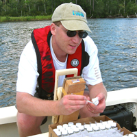 Dr. Brush samples nutrients from the New River Estuary, N.C., as part of a project funded by the Department of Defense.
