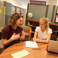 Aleina Kreider (L) works with a student.