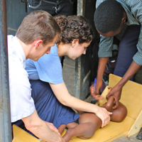 Ickes and Emily Mahoney '15 measure a child at a nutrition clinic in Bundibugyo, Uganda