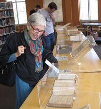 "Science author Dava Sobel looks over the display of rare science books—including a first edition of Newton's ""Principia""—brought to the Physics Library from Swem Library's Special Collection Research Center. Photo by Joseph McClain."