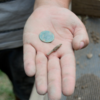 A slate pencil fragment, one of 40-some found at the site, came out of the sifter along with a bonus find—a 1773 British coin. (photo by Joseph McClain)