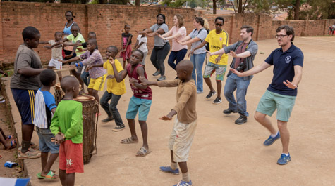 College students dance with children in an outdoor location