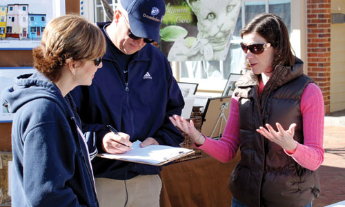Katie Moriarty, an M.B.A. student at the Mason School of Business at the College of William & Mary, discusses the idea of a community-supported fishery with a pair of festival-goers during the 2nd Sundays Williamsburg Arts and Music Festival in March
