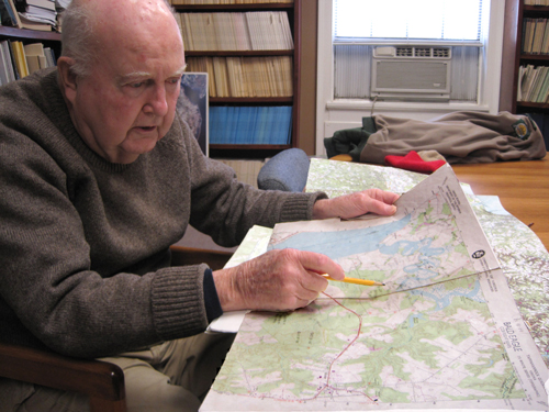 Back on the ground, Mitchell Byrd reviews locations of active bald eagle nests on topographic maps.