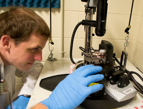 Sean Kobeley adjusts an atomic force microscope used in the molecular study of silk. Atomic force microscopy is a specialty of the lab of Hannes Schniepp.